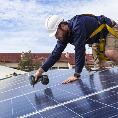 Man installing solar panels on house roof